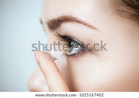Photo of  Close-up shot of young woman wearing contact lens.