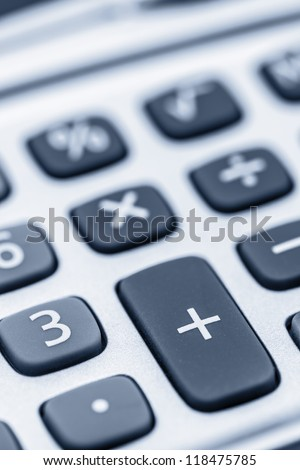 Close-up shot on a calculator keyboard with focus on the plus key.