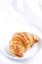 close up shot on fresh croissant on white ceramic plate placed on creased of blank white fabric, vertical image, copy space concept.