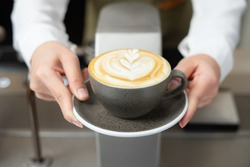 Close up shot on front view of barista girl hands serving beautiful flower shape on fresh latte art in coffee cup on dark grey plate pass over coffee maker machine at coffee shop and cafe restaurant.