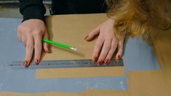 Close up shot - professional woman decorator, designer working with kraft paper and making envelope at workshop, studio - top view. Design, handmade and art concept