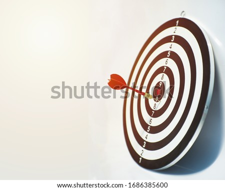 Close up shot red darts arrows in the target ,arrow hitting the center of a shooting target for business close targeting and good success.Business target or goal success and winner concept.
