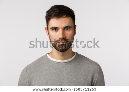 Close-up shot serious and determined handsome, adult masculine bearded man in grey sweater, looking with casual expression camera, standing still, awaiting important news, white background Сток-фото ©
