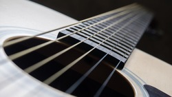 Close up shot sound hole and strings of acoustic guitar