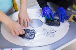 Close up shot - stencil painting: women hands painting wooden circle. Paint, handmade and crafting work concept