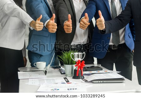 Close up shot  team of businesspeople give thumbs up over the trophy in meeting with notebook and paper charts. Good teamwork , Goal setting and work commitment concept. #1033289245