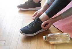 Close up shot view of fit woman tie shoelaces while doing workout at home. Bottle of water. Athletic female tying the laces on shoes while taking break between training at home.