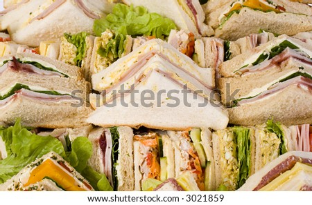 Close up shots of assorted sandwich triangles on a catering party platter