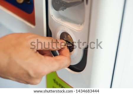 Close-up shots of the hands that are wearing coins into the vending machine.