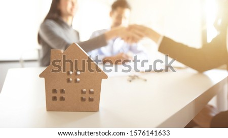 Close-up shots of the model key with groups of people are made of real estate purchase contract is in the background.