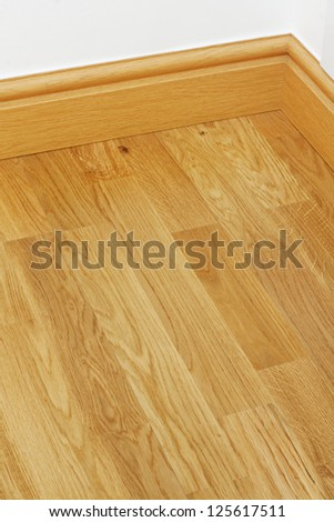 Close up showing some wood effect vinyl flooring and mdf imitation pine skirting boards in new - Linoleum imitation parquet ...