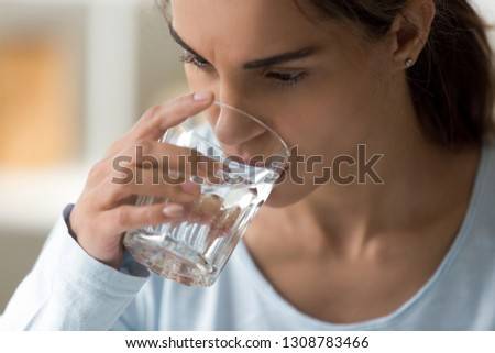 Close up sick young woman holds glass, unhealthy female feeling thirsty drinking still clear water preventing of dehydration normally function in body and clear toxins. Healthy lifestyle habit concept