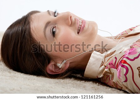 Close up side portrait of a young beautiful woman listening to music with her earphones while laying down on a furry carpet at home.