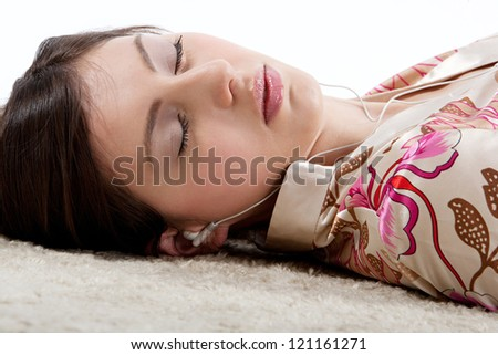 Close up side portrait of a young beautiful woman listening to music with her earphones while laying down on a furry carpet at home with her eyes closed.