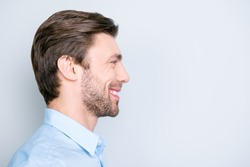 Close up side portrait of young, bearded, happy, smiling manager standing over grey background with copy space
