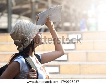 Close up, side pose of Asian female tourist wearing hat and backpack using city map blocking sunlight on sunny hot day.