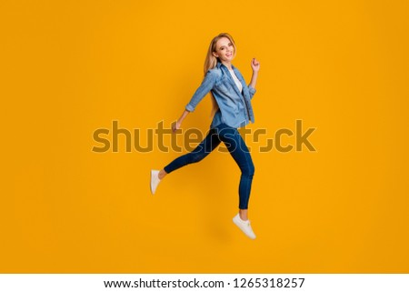 Close up side profile full length body size photo of attractive active cheer her lady jumping high going straight ready for sale wearing casual jeans denim shirt isolated on yellow bright background
