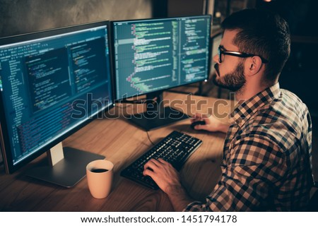 Close up side profile photo handsome he him his guy brainstorming briefing coder typing php css keyboard development outsource IT two monitors table office agency wear specs formalwear plaid shirt