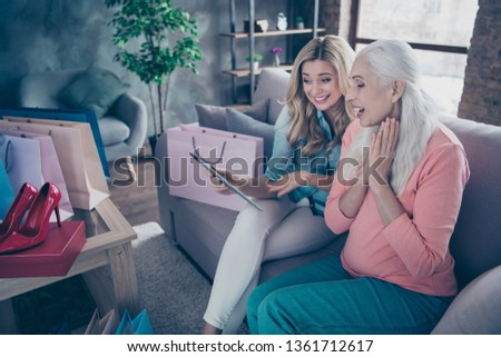 Close up side profile photo two beautiful people she her ladies granny granddaughter relatives shop mood look clothes tablet hand arm online lazy buy buyer easy way sit couch divan sofa house indoors