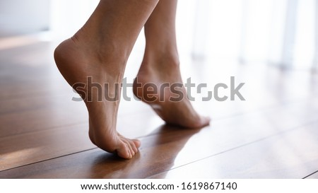Close up side view beautiful female feet with perfect smooth skin standing tiptoe on warm wooden floor with underfloor heating, barefoot young woman walking at home, enjoying morning, relaxing ストックフォト ©