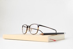 Close up side view book with pencil and glasses on white background