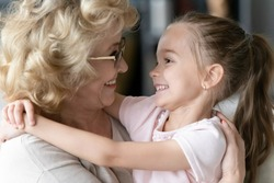 Close up side view faces of loving little girl hugs with love showing sincere strong attachment to old grandma looking at each other feeling affection gratitude for protection and candid bond concept