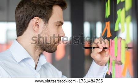 Close up side view focused businessman writing on colorful sticky notes attached on glass wall, entrepreneur create visual to-do list, future career business goals, daily aims, completed tasks concept