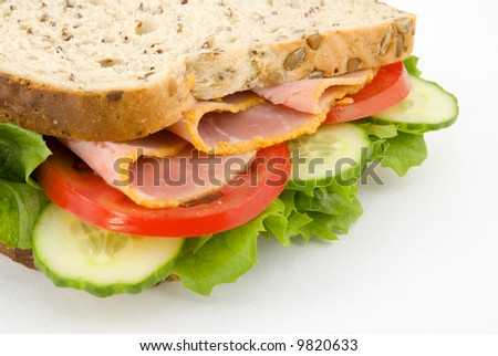 Close up side view of a ham and salad sandwich