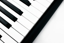 Close-up side view of synthesizer on white background. Digital keyboard. Musical instrument. Black and white piano keys. Entertainment concept. Web, social media banner template. Stock photo.