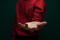 Close-up side view of the hands of an unidentified young man in a dark shirt and jacket holding an invisible object on palm. The concept of caring hands. Advertising concept