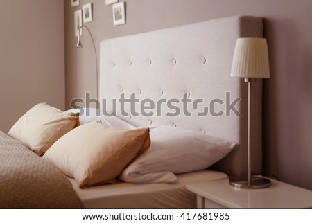 Close up side view of the pillows and headboard of an empty double bed with brown and beige linen