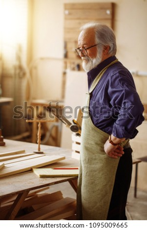 close up side view portrait of old joiner with white hair, moustache nad beard resting in the workroom