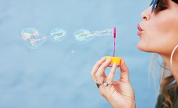 Close up side view shot of young female model blowing soap bubbles on blue background. Focus on hands and wand.