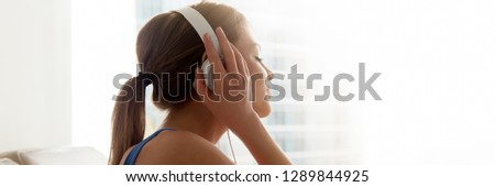 Photo of Close up side view woman closing eyes wearing headphones listening music enjoy favorite song resting at home. Leisure concept horizontal photo banner for website header design with copy space for text