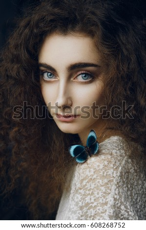 Close up silent portrait of dreaming girl with blue eyes and curly hair in cold morning light, wearing white dress with blue butterfly seating on her shoulder. She is watching at the camera.