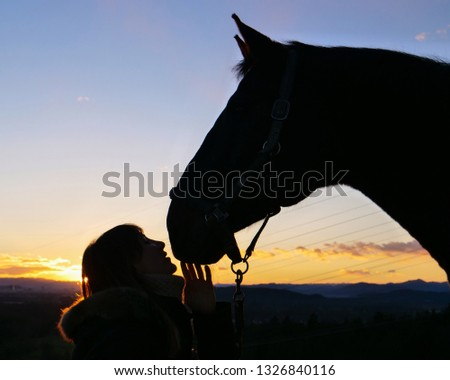 CLOSE UP, SILHOUETTE: Gentle Caucasian woman whispering to her stallion on a tranquil spring morning. Beautiful shot of happy girl gently caressing and bonding with her majestic horse at sunrise. #1326840116
