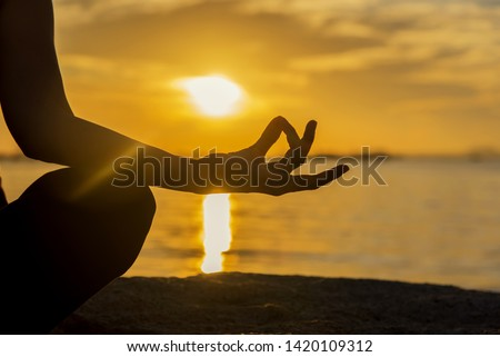 Close up Silhouette hands. Woman do yoga outdoor. Woman exercising vital and meditation for fitness lifestyle club at the sunset beach background. Healthy Concept