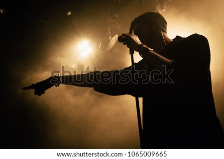 Close-up silhouette of a singer on the stage. Smoke and yellow stage lights in the background.