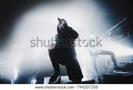 close up silhouette of rap & trap & hip hop star / singer perform on stage of nightclub. Dark background, smoke, concert  spotlights