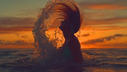 CLOSE UP, SILHOUETTE: Unrecognizable young woman splashes ocean water with her long hair at breathtaking sunset. Playful girl in bikini whips her head back and sprays water in the orange evening sky.