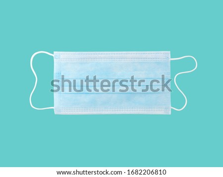Photo of  close up single light blue surgical mask (medical face mask) with white rope strap for prevent germs while performing surgery or protective coronavirus (COVID-19) outbreak isolated on cyan background