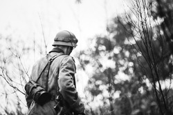 Close Up Single Re-enactor Dressed As German Wehrmacht Infantry Soldier In World War II Walking In Patrol Through Autumn Forest. WWII WW2 Times. Photo In Black And White Colors.