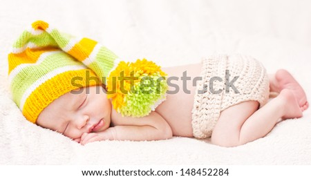 Close-up sleeping newbornon a white background with bright hat - stock photo