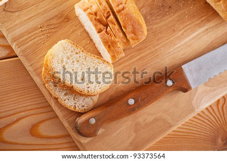 Close-up sliced ??bread (long loaf) on cutting wooden board, knife