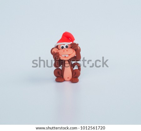 Close up Small cute clay cartoon monkey handmade wear red Christmas hat and naughty funny face to tease on white background for kid , interior garden decoration , green rawmaterial