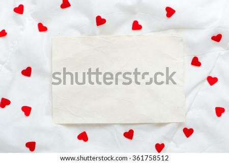 Close up Small White Card with I Love You Message and Red Rose Flower on Top of the white soft silk or blanket. #361758512