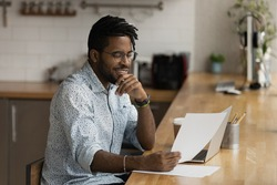 Close up smiling African American man wearing glasses reading good news in letter, holding paper, sitting at table with laptop, received job promotion, money refund, working with correspondence