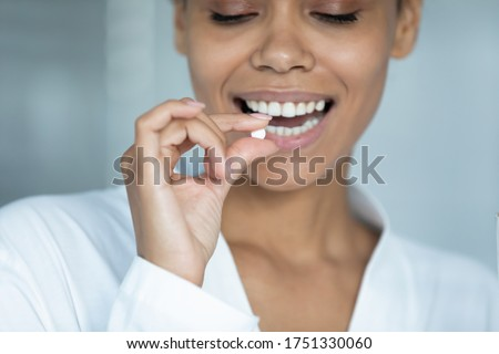 Close up smiling African American young woman holding white round pill, beautiful girl wearing white bathrobe taking supplements or vitamins in morning, healthcare and treatment concept