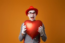 Close up smiling clown mime in red hat and vest holds heart ball in his hands