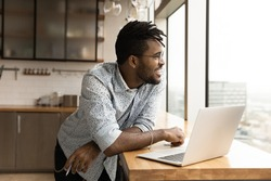 Close up smiling dreamy African American man wearing glasses distracted from laptop, looking out window, dreaming about good future, visualizing new opportunities, pondering online project strategy